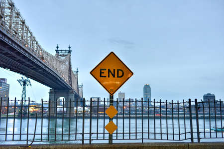 queensboro bridge: End of Street sign with a view of the Queensboro Bridge from Manhattan, New York at dusk. Stock Photo