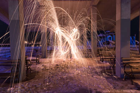 Showers of hot glowing sparks from spinning steel wool at Coney Island Beach, Brooklyn, New York. Reklamní fotografie