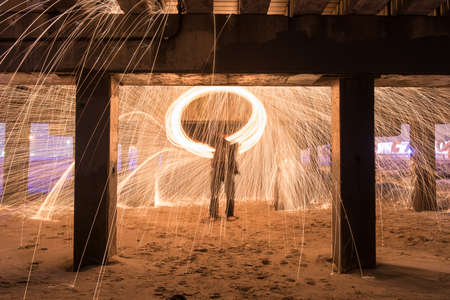Showers of hot glowing sparks from spinning steel wool at Coney Island Beach, Brooklyn, New York. photo