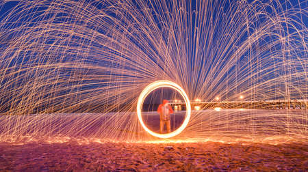 steel: Showers of hot glowing sparks from spinning steel wool at Coney Island Beach, Brooklyn, New York. Stock Photo
