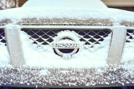 front end: BROOKLYN, NEW YORK - MARCH 1, 2015: Front end of a Nissan pickup truck during a winter storm.