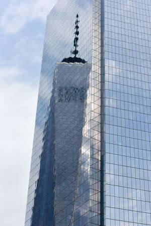 wtc: New York, NY - April 5, 2015: One World Trade reflecting off of Four World Trade Center in lower Manhattan.
