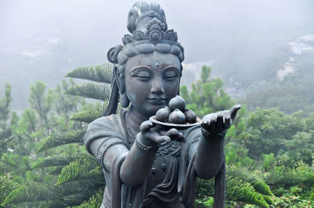 neighboring: Statue neighboring Tian Tan Buddha shrouded in fog. Stock Photo