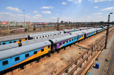 mandela: Johannesburg, South Africa - March 26, 2012: The Braamfontein Railway Yards with their colorful cars under the Nelson Mandela Bridge. The yards lie between Newtown and Braamfontein.