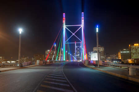 Nelson Mandela Bridge at night. The 284 meter long Nelson Mandela Bridge, officially opened by Nelson Mandela himself, which crosses over the 40 railway lines that lie spread beneath its span.