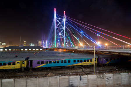 gauteng: Nelson Mandela Bridge at night. The 284 meter long Nelson Mandela Bridge, officially opened by Nelson Mandela himself, which crosses over the 40 railway lines that lie spread beneath its span.