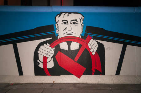 Berlin, Germany - November 7, 2010: Artistic graffiti painting of Gorbachev, called the East Side Gallery, line a 1.3 km long section of the Berlin Wall (Berliner Mauer) near the river Spree at night.