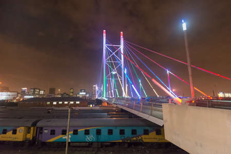 precinct: Nelson Mandela Bridge at night. The 284 metre long Nelson Mandela Bridge, starts at the end of Jan Smuts Avenue and linking Braamfontein to the Cultural precinct in Newtown. Editorial