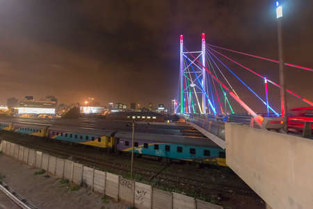 precinct: Nelson Mandela Bridge at night. The 284 metre long Nelson Mandela Bridge, starts at the end of Jan Smuts Avenue and linking Braamfontein to the Cultural precinct in Newtown. Stock Photo