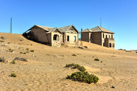 The abandoned ghost diamond town of Kolmanskop in Namibia, which is slowly being swallowed by the desert. Stock Photo