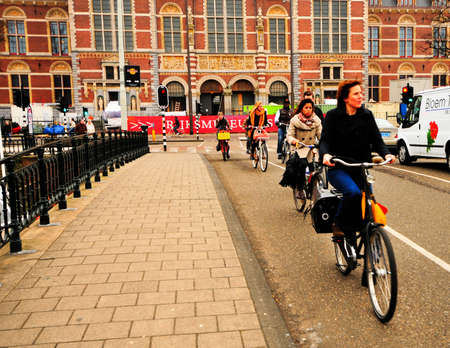 dutch: Amsterdam, Netherlands - February 24, 2012: Locals bicycling past the Rijksmuseum.