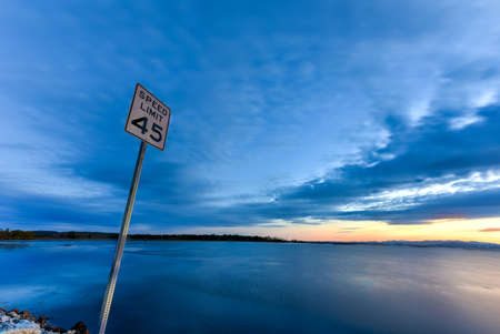 mph: Lake Champlain between New York and Vermont at sunset. Speed limit sign as seen off of the highway, 45 MPH.