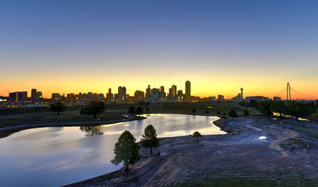 Downtown Dallas skyline at sunrise in Texas, USA from the Trinity River.