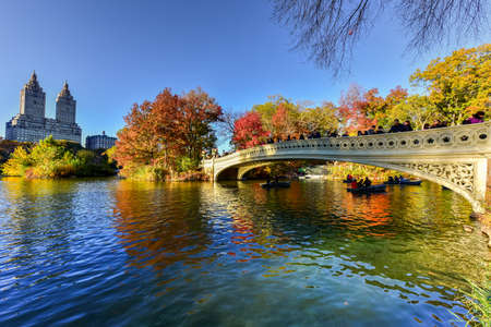 The Bow Bridge is a cast iron bridge located in Central Park, New York City, crossing over The Lake and used as a pedestrian walkway in autumn. Stock Photo