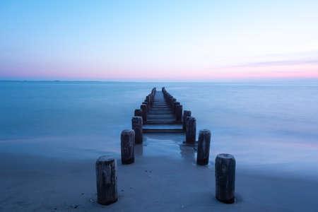 coney: Pier along a dramatic sunset on Coney Island Beach in Brooklyn, New York.