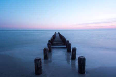 Pier along a dramatic sunset on Coney Island Beach in Brooklyn, New York.
