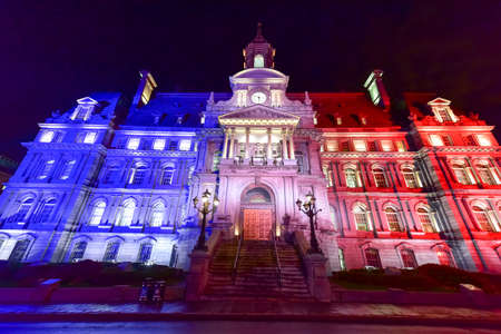election night: Main Building of the City Hall in Old Montreal illuminated in the colors of France, blue, white, and red.