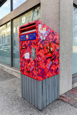 canada stamp: Canada Post mailbox in Montreal, Quebec, Canada covered in graffiti and stickers.