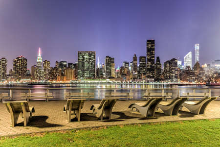 city park skyline: Benches along Gantry Park with the New York City skyline view in the background.