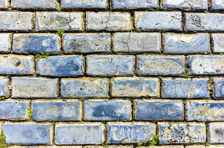 bottoms: Blue cobblestone paved street in Old San Juan, Puerto Rico. They were brought as ballast in the bottoms of European merchant ships in the 1700s. Stock Photo
