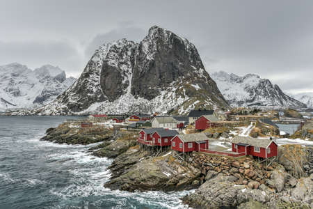rorbuer: Fishing hut (rorbu) in the Hamnoy and Lilandstinden mountain peak in winter in Reine, Lofoten Islands, Norway.