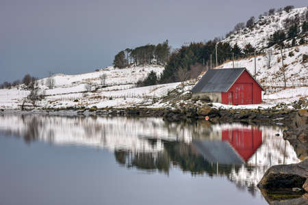 rorbuer: Rorbuer reflected along Vagspollen in the Lofoten Islands, Norway in the winter.