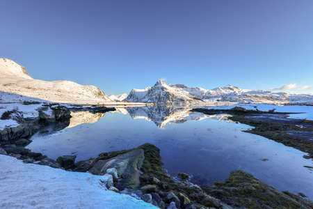 bo: Boosen by Bo with mountains reflecting in the water. In the Lofoten Islands, Norway in the winter. Stock Photo