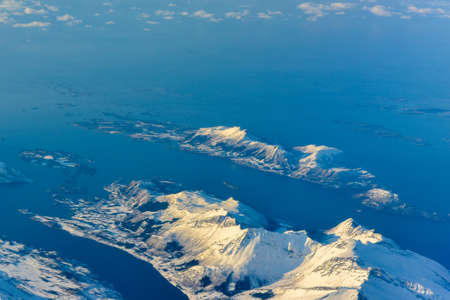 snow covered mountains: An aerial view of the snow covered mountains of the fjords of Norway in the winter.