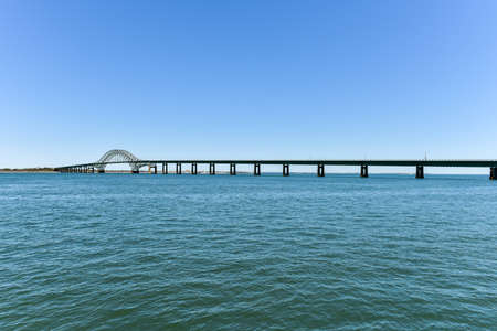 inlet: The Fire Island Inlet Bridge, an integral part of the Robert Moses Causeway, is a two-lane, steel arch span with a concrete deck that carries the parkway over Fire Island Inlet. Stock Photo