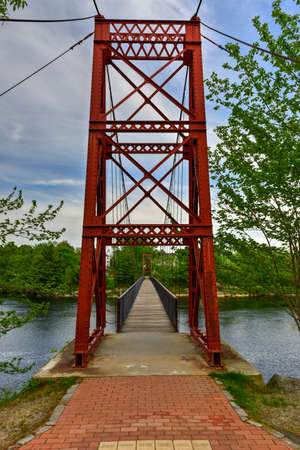 neighboring: The Androscoggin Swinging Bridge is a pedestrian suspension bridge spanning the Androscoggin River between the Topsham Heights neighborhood of Topsham, Maine and neighboring Brunswick. Stock Photo