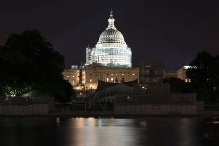 The US Capitol Building under scaffolding as seen across the reflecting pool at night in Washington, DC. Zdjęcie Seryjne