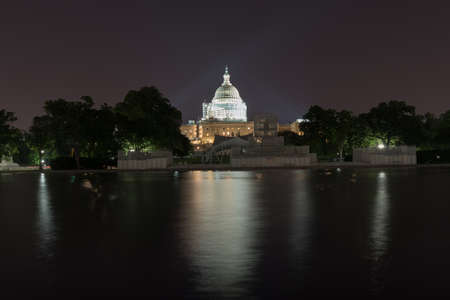 us capitol: The US Capitol Building under scaffolding as seen across the reflecting pool at night in Washington, DC. Stock Photo