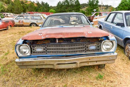 junk: Rusting old car in a desert junk yard.