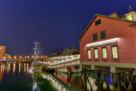 boston tea party: The Boston Tea Party Museum, in Boston Harbor in Massachusetts, USA with its mix of modern and historic architecture at night. Stock Photo