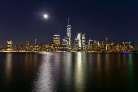 New York skyline as viewed across the Hudson River in New Jersey at dusk with the super moon in the background.