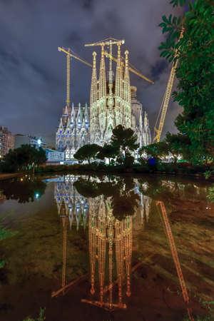 La Sagrada Familia in der Nacht beleuchtet, im Wasser reflektiert. Die Kathedrale wurde von Antoni Gaudi entworfen und ist seit 1882 in Barcelona, ??Spanien im Bau. Standard-Bild - 71693860