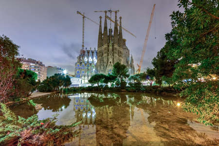 La Sagrada Familia illuminated at night, reflecting in the water. The cathedral was designed by Antoni Gaudi and has been under construction since 1882 in Barcelona, Spain. Editorial