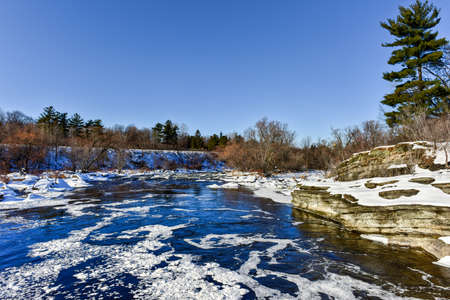 Hogs Back falls located on the Rideau River in Hogs Back park in Ottawa, Ontario Canada frozen over in winter.