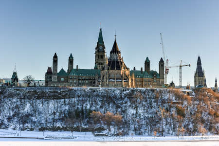 Parliament Hill and the Canadian House of Parliament in Ottawa, Canada across the frozen Ottawa River during wintertime. Stock Photo