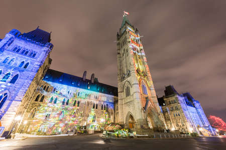 Winter holiday light show projected at night on the Canadian House of Parliament to celebrate the 150th Anniversary of Canada in Ottawa, Canada.
