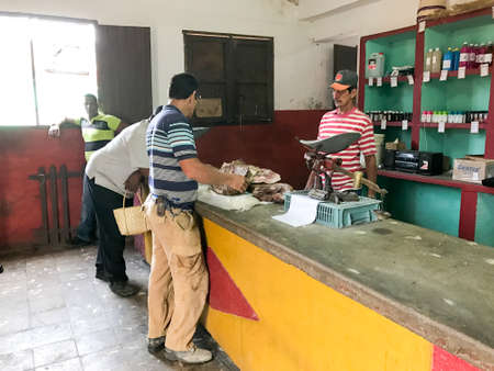 housewares: Trinidad, Cuba - January 12, 2017: Buying meat in a shop on the streets of Trinidad, Cuba.