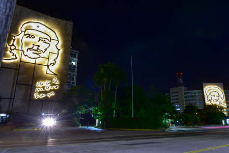 ministry: Portraits of Che Guevara and Camilo Cienfuegos on the Ministry of the Interior and the Ministry of Informatics and Communications by the Plaza de la Revolucion in Havana, Cuba at night.