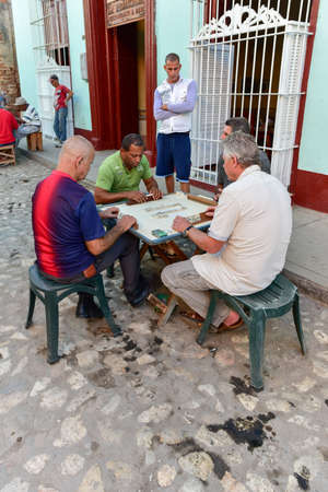 Trinidad, Cuba - January 12, 2017: Old men playing dominoes in the streets of Trinidad, Cuba.