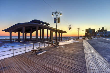 Coney Island Boardwalk with Parachute Jump in the background in Coney Island, NY. The boardwalk was built in 1923 and stretches for 2.51 miles
