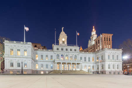 New York City Hall at night, the seat of New York City government, located at the center of City Hall Park in the Civic Center area of Lower Manhattan, between Broadway, Park Row, and Chambers Street. Stock Photo