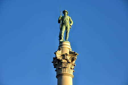 Confederate Soldiers & Sailors Monument. It depicts a bronze Confederate private standing on top of the pillar, which is composed of 13 granite blocks to symbolize each of the Confederate states.