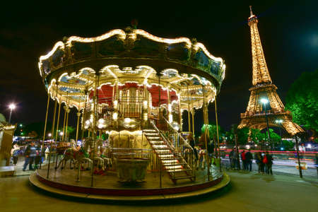 Illuminated vintage carousel close to Eiffel Tower in Paris, France.