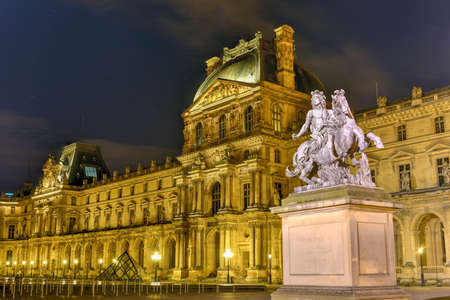 Statue of King Louis XIV with the Louvre Museum at night in the background Editorial