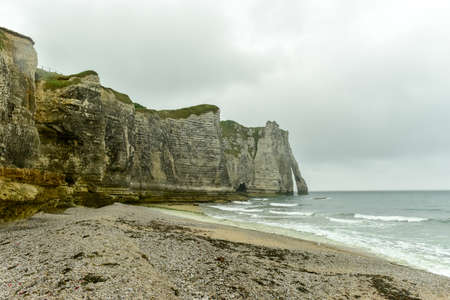 Spectacular natural cliffs Aval of Etretat and beautiful famous coastline on a cloudy day in Normandy, France, Europe. Stock Photo