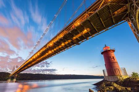ジョージ ワシントン ブリッジと夕方フォート ワシントン公園、ニューヨーク、ニューヨークの赤の小さな灯台です。 写真素材